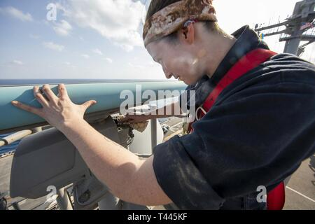 U.S. 5TH FLEET AREA OF OPERATIONS (March 17, 2019) Electronics Technician 3rd Class Sara Head inspects the SPS-73 radar aboard the Wasp-class amphibious assault ship USS Kearsarge (LHD 3). Kearsarge is the flagship for the Kearsarge Amphibious Ready Group and, with the embarked 22nd Marine Expeditionary Unit, is deployed to the U.S. 5th Fleet area of operations in support of naval operations to ensure maritime stability and security in the Central Region, connecting the Mediterranean and the Pacific through the western Indian Ocean and three strategic choke points. - Stock Image