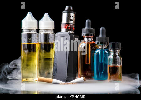 Modern vaporiser versus old tobacco cigarette in smoke - Stock Image