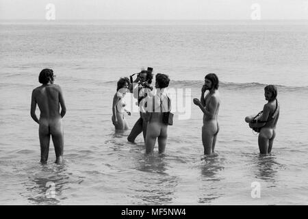 A TV crew at the 1970 Isle of Wight pop festival,  filming hippies skinny dipping in Freshwater Bay for a news report. Hippy guards had ordered all members of the press wanting access to the bay to strip naked themselves before filming or photographing, which the bravest members of the media cheerfully did. - Stock Image