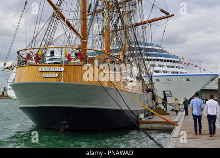 The three-masted barque Kaskelot, a wooden Tall Ship, at the Southampton Boat Show (2018) with a cruise ship docked in the background. - Stock Image