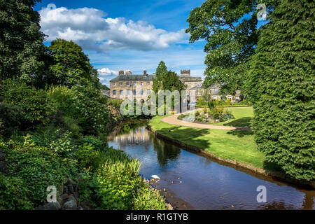 Picturesque view of typical stone buildings in Buxton from the park gardens. - Stock Image