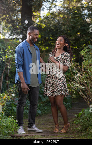 An African couple laughing together in a garden - Stock Image