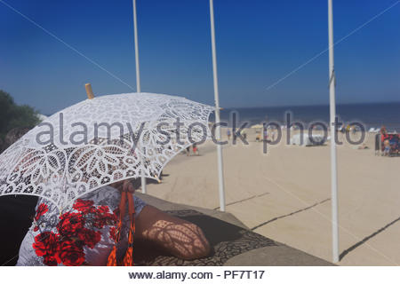 Woman with lace umbrella on the beach - Stock Image