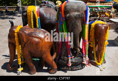 Wood carved elephants at Thai Buddhist Buddhist temple devoted to sacred elephants at Cape Promthep. - Stock Image