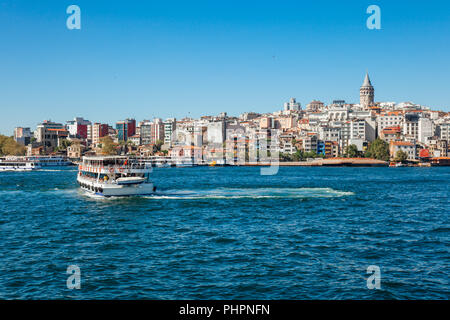 A tourist boat sails across the Golden Horn, Istanbul, Turkey - Stock Image