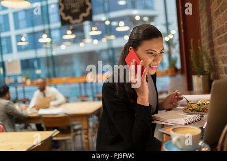 Smiling businesswoman talking on smart phone and working at laptop in cafe - Stock Image