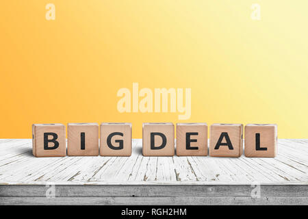 Big deal sign made of wooden cubes on a desk with a yellow wall in the background - Stock Image