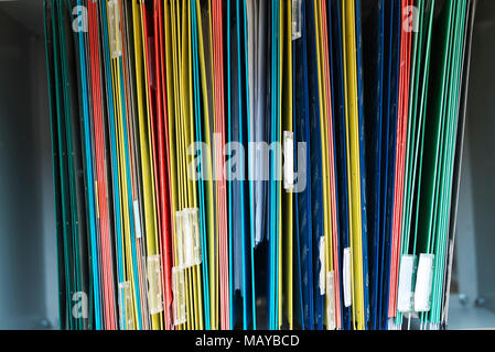 Files in an office filing cabinet stacked with personal information - Stock Image