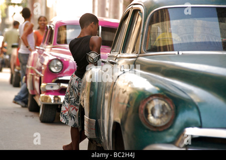 Classic American cars in the street. A cultural icon for modern day Cuba. Havana, Cuba - Stock Image