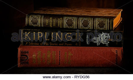 Three stacked vintage classic books closed on a desk - litereracy concept - Stock Image
