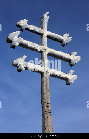 Frozen summit cross on top of a mountain in the Dolomite Alps - Stock Image