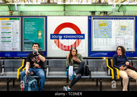 People sit on a bench on the platform at South Kensington London Underground Station. - Stock Image