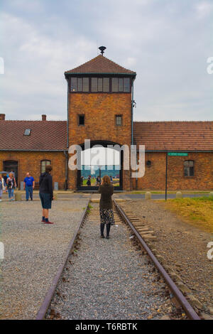 Oswiecim, Poland - July 11th 2018.  A visitor takes photographs of the main entrance and guard tower at the Birkenau-Auschwitz II concentration camp - Stock Image