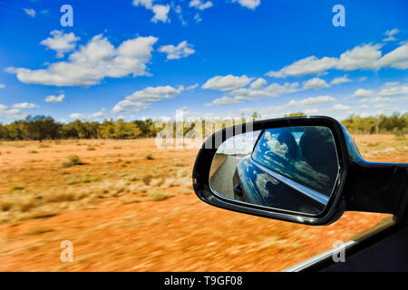 Australian outback red soil and scarse gum-trees under blue sky with rear view mirror through driving car blurring road side. - Stock Image