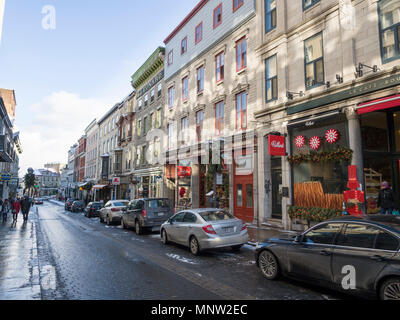 Commerical Street in Old Quebec -- winter: A line of old stone and brick buildings, now bakeries and stores, on a cobbled street in Quebec City in winter.  Parked cars on one side and pedestrians walk the sidewalk. - Stock Image