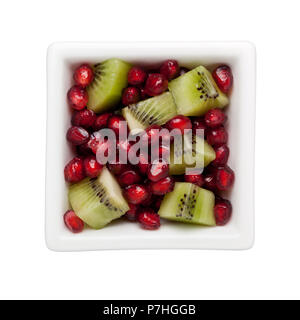 Pomegranate arils and diced kiwifruit in a square bowl isolated on white background - Stock Image