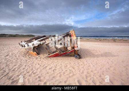 Old shipwrecked boat on a beach - Stock Image