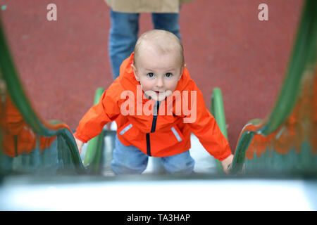 Smiling Cute Baby Boy With Orange Raincoat Climbing Up The Slide, Close Up Portrait View - Stock Image
