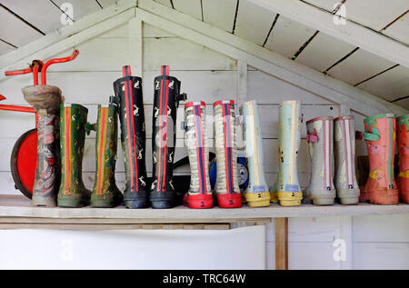 children's rubber boots on shelf in summer house, north norfolk, england - Stock Image