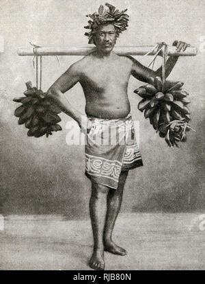 Man carrying fruit on a pole, Tahiti, French Polynesia. - Stock Image