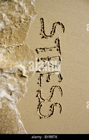 'Stress' written out in wet sand, being washed away by the sea. Please see my collection for more similar - Stock Image