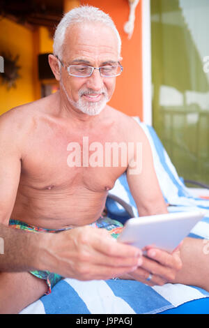 Older man around 60 using tablet computer for reading on vacation - Stock Image