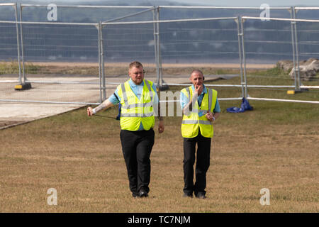 two male security guards wearing high visibility vests at an outdoor event - Stock Image