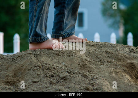 A child stands with bare feet on a pile of dirt. - Stock Image