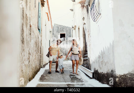 A family with two toddler children walking in town on summer holiday. A father and mother with son and daughter in baby carrier on a narrow street. - Stock Image