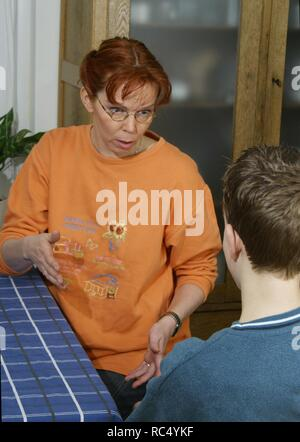 2000s: Over 40 mother and teen son having a discussion at the table - Stock Image