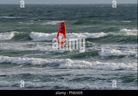 East Wittering, UK. 19th September 2018. Windsurfer(s )brave wild, wet and windy weather  of Storm Ail - our first named storm of the season. Weather was  recorded at the Chichester Bar at 3pm BST  a mean speed of 29 Knots highest gusting  35 .4 Knots The Met Office have issued an yellow weather warning for this area with strong winds and heavy rainfall.Credit Gary Blake / Alamy Live News - Stock Image