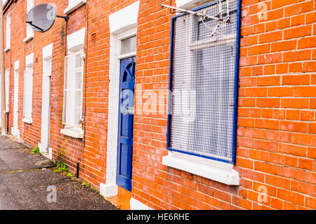Steel grilles on the windows of houses, to protect against vandalism, in an interface area of Belfast. - Stock Image