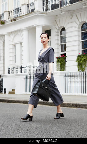 Chic young woman in grey jumpsuit crossing London street - Stock Image
