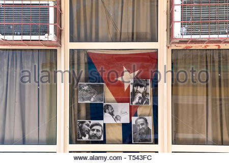 A Cuban flag and photos of Fidel Castro in an office windows. After his passing, Fidel Castro pictures can be found in the most dissimiles places. - Stock Image