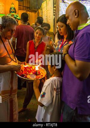 Hindu Priest with Family Performing Ritual of Touching the Lamp, Sree Veera Hanuman Hindu Temple, Kuala Lumpur, Malaysia. - Stock Image