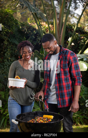 A couple barbecuing food together - Stock Image