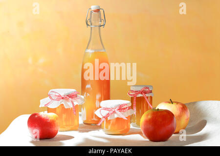 Homemade apple juice in a glass bottle and jelly in jars with linen covers and a nostalgic ribbon bow in bright sunshine in front of an orange wall. - Stock Image