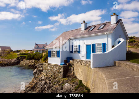 Traditional Welsh white and blue cottage overlooking a rocky cove in coastal village. Rhoscolyn, Holy Island, Anglesey, North Wales, UK, Britain - Stock Image
