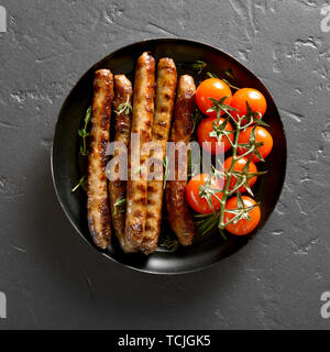 Roasted sausages and cherry tomatoes on plate over black stone table. Top view, flat lay - Stock Image
