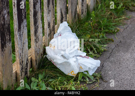 A discarded single-use plastic carrier bag on a grass verge against a wood slat fence - Stock Image