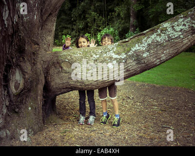 Boy and girl hide behind tree branch - Stock Image