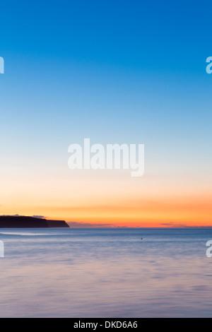 Whitby at sunset looking towards Runswick Bay. - Stock Image