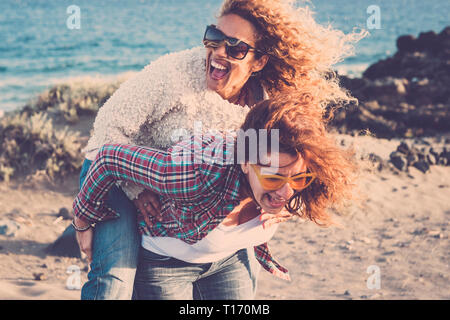 People laughing a lot and have fun together in friendship in outdoor leisure activity - couple of women gone crazy carrying eachother on the shoulder  - Stock Image