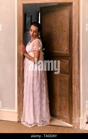 Young lady in authentic regency dress standing in a doorway - Stock Image