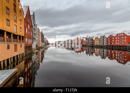 Colourful wooden buildings on the edge of river channels in the town of Trondheim in Norway. - Stock Image