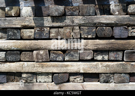 Cubed stack of aged railroad railway sleepers covered in creosote - Stock Image