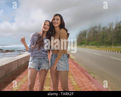 Two women standing together on a footpath beside sea - Stock Image