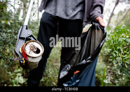 closeup of a caucasian man collecting garbage with a trash grabber stick, in a forest, as an action to clean the natural environment - Stock Image