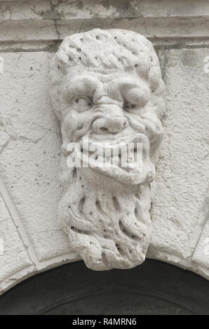 A Gargoyle face on a bridge in Venice - Stock Image