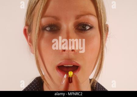 Pill on tongue   Ref: CRB425_10046_104  Compulsory Credit: Synercomm/Photoshot - Stock Image